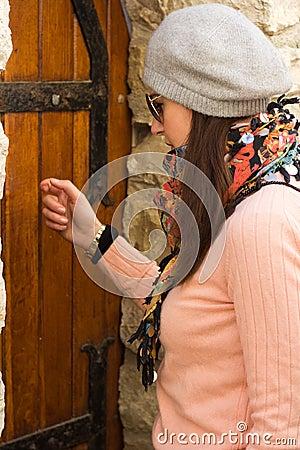 Women Knocking On An Old Wooden Door