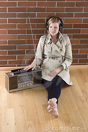Women listens to an old radio
