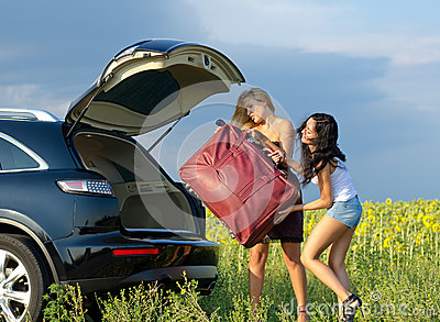 Women loading a heavy bag into car