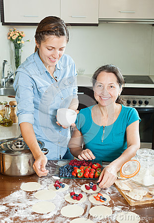 Women making sweet vareniki with berries