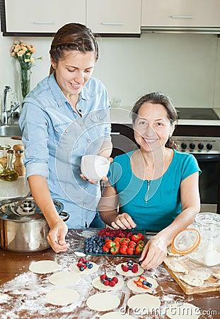 Women making sweet vareniki with berries