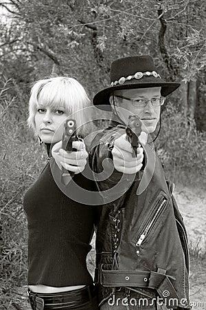 Women and man back-to-back aiming handguns