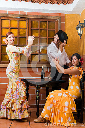 Women and man in traditional flamenco dresses dance during the Feria de Abril on April Spain