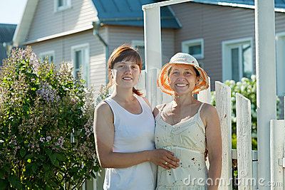 Women near fence wicket of home
