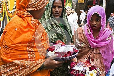 women offering flowers in Muslim shrine