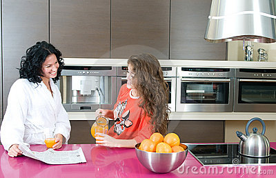 Women with orange juice at kitchen
