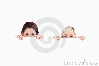 Women peeking over a banner