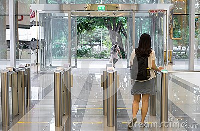 Women people walking out from security at an entrance gate with key card access control smart office building Editorial Stock Photo