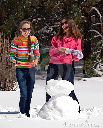 Women playing with snowman