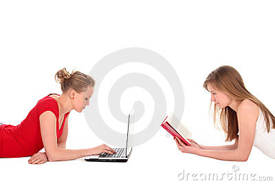 Women reading book and using laptop