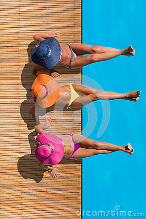 Women reaxing on the deck by the swimming pool