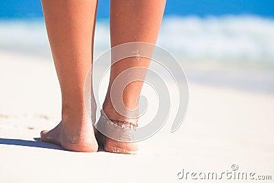 Women s beautiful smooth legs on white sand beach