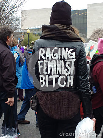 Free Women`s March On Washington DC, Woman Walking Through The Crowd Wearing A Jacket Labeled `Raging Feminist` Royalty Free Stock Photos - 84620008