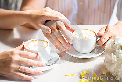 Women s and men s hands with wedding rings, at the cafe table wi