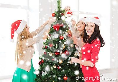 Women in santa helper hats decorating a tree