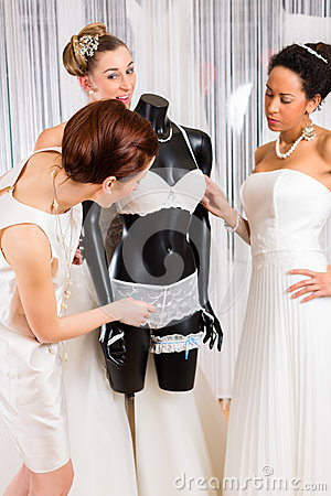 Women selecting bridal lingerie in wedding shop stock for What undergarments for wedding dress shopping