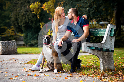 Women Sitting Outdoors With Her Pet Dog German Boxer