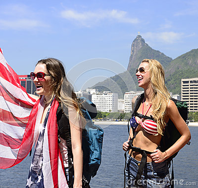 Women sport fans holding USA Flag in Rio de Janeiro with Christ the Redeemer in background.