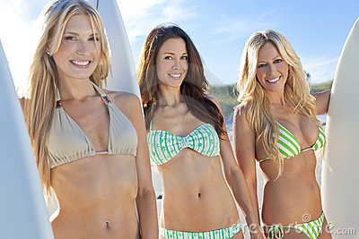Women Surfers In Bikinis With Surfboards At Beac