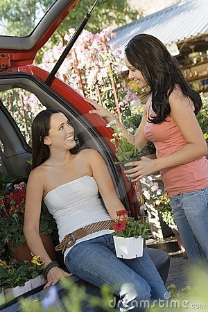 Women talking in garden centre at open car trunk