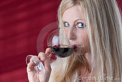 Women tasting red wine.