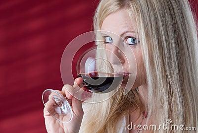 Women tasting red wine.