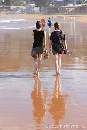 Women walking barefoot on beach