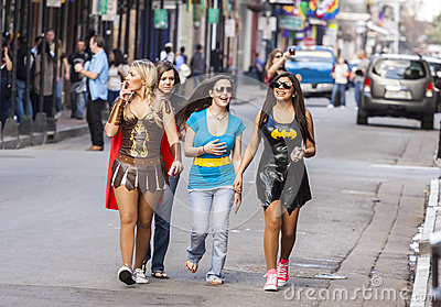Women wearing funny costumes celebrating famous Mardi Gras carnival on the street in French Quarter. Editorial Photography