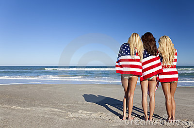 Women Wrapped in American Flags on a Beach