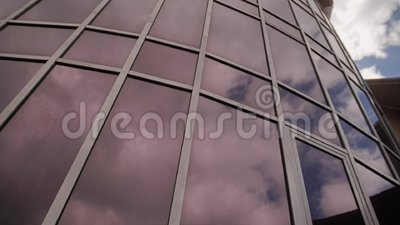 A wonderful building made of glass with reflections of the sky and clouds in it. Beautiful urban architecture stock video footage