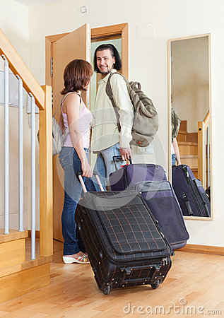 Wonderful couple together with their luggage leaving home
