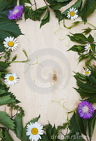 Wood background with green foliage and flowers