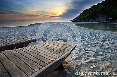 Wood bed on beach in dusky sky