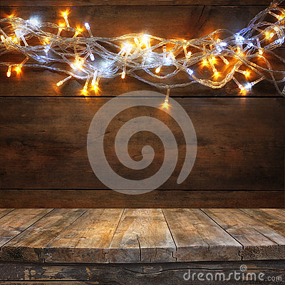 Free Wood Board Table In Front Of Christmas Warm Gold Garland Lights On Wooden Rustic Background. Filtered Image. Selective Focus Stock Photography - 59716122