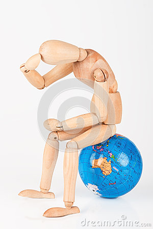 Wood mannequin sitting on top of a world globe to protect isolated concerned Stock Photo
