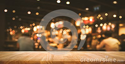 Wood table top Bar with blur light bokeh in dark night cafe Stock Photo
