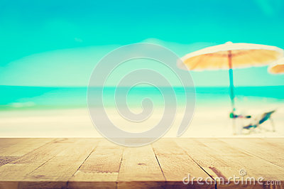 Wood table top on blurred blue sea and white sand beach background Stock Photo