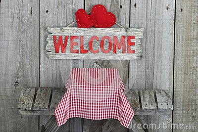 Wood welcome sign with hearts over picnic table