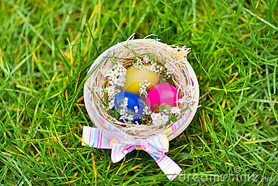 Wooden basket with colorful Easter eggs and flowers Stock Photo