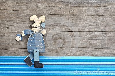 Wooden blue rabbit decoration on grey wooden background with blu