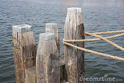 Wooden bollard with rope of tied ship