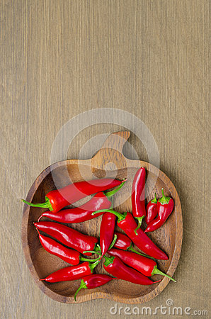 Wooden bowl with red chili peppers (and space for text) top view
