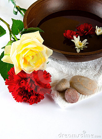 Wooden bowl with white towel and scattered pebbles