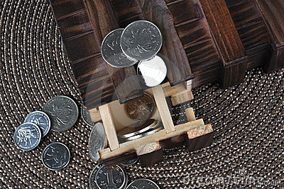 Wooden box and coins on grass intertexture