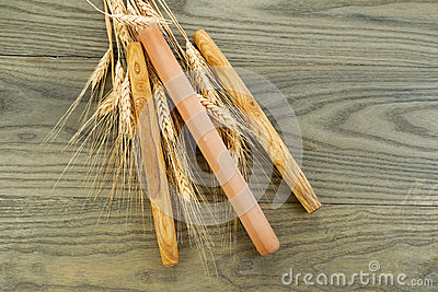 Wooden Bread Rollers with Dried Wheat Stalks on fading wood
