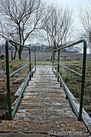 Wooden bridge with green handrail during winter
