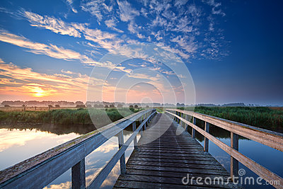 Wooden bridge over river at sunrise