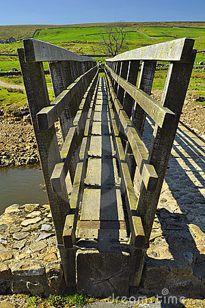 Wooden bridge over stream in countryside