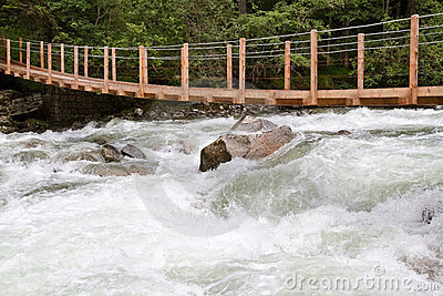 Wooden bridge over wild waters