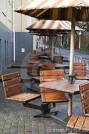 Wooden cafe chairs, tables and umbrellas